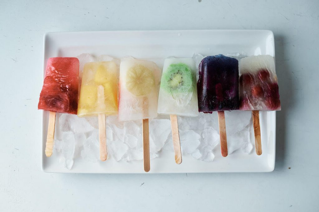 rainbow popsicles laid out in color order on plate of ice