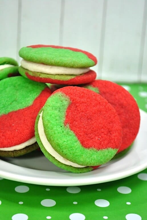 plate of red and green sandwich cookies with frosting in the middle.
