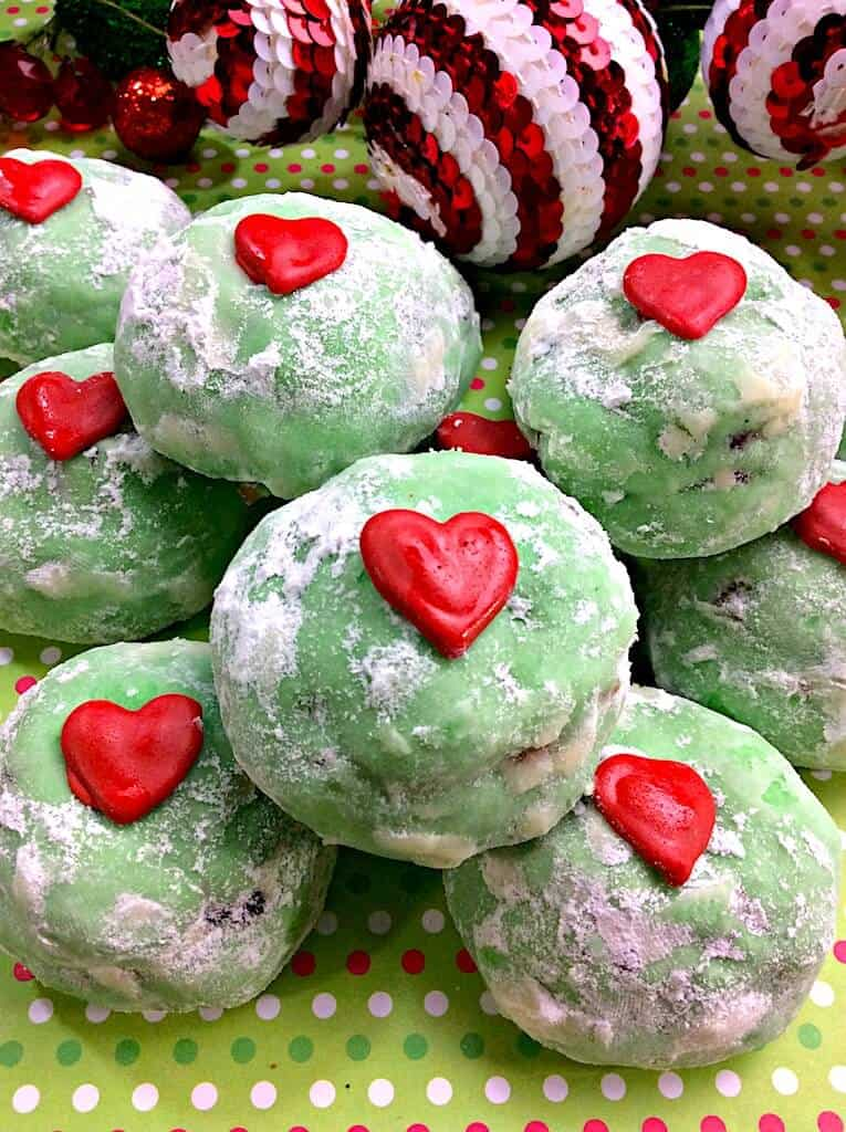 Green grinch snowball cookies with red heart stacked on each other