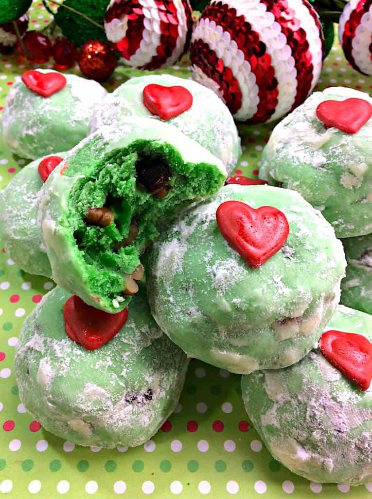 Green Snowball cookies with red heart and bit taken out of one cookie
