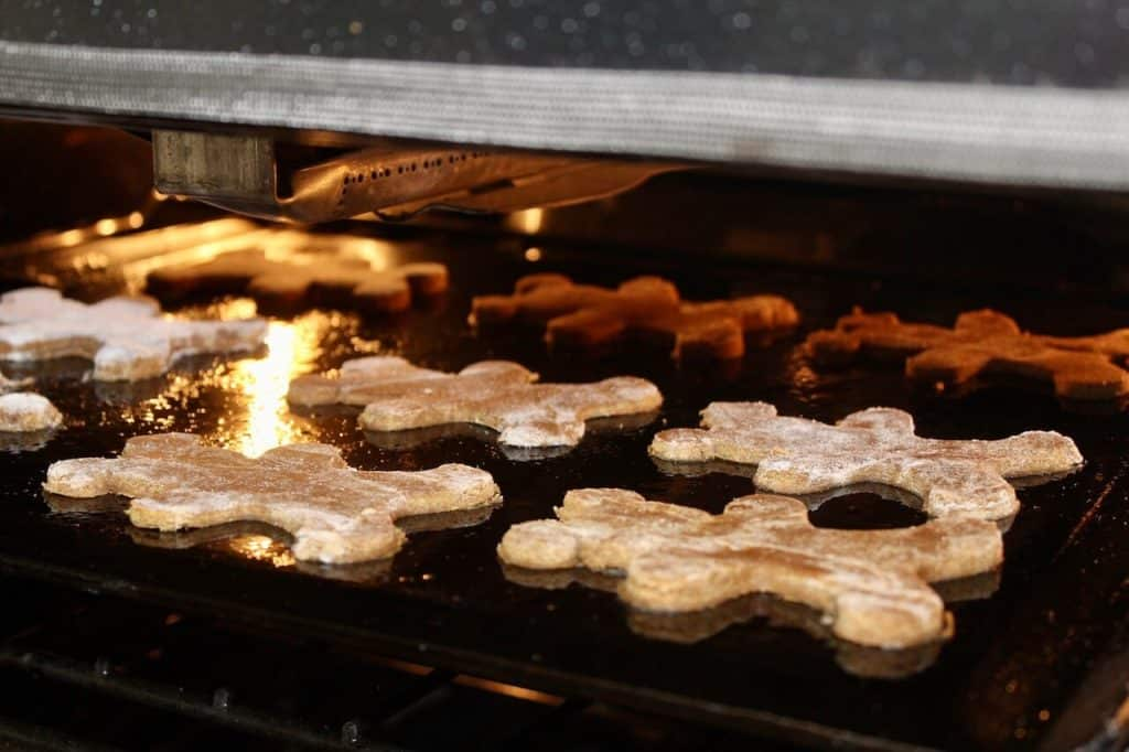 gingerbread men on a cookie sheet in oven