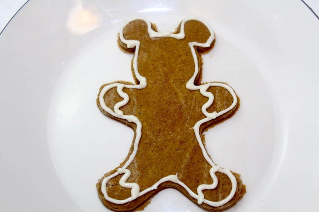 Mickey shaped gingerbread man with white frosting along edge