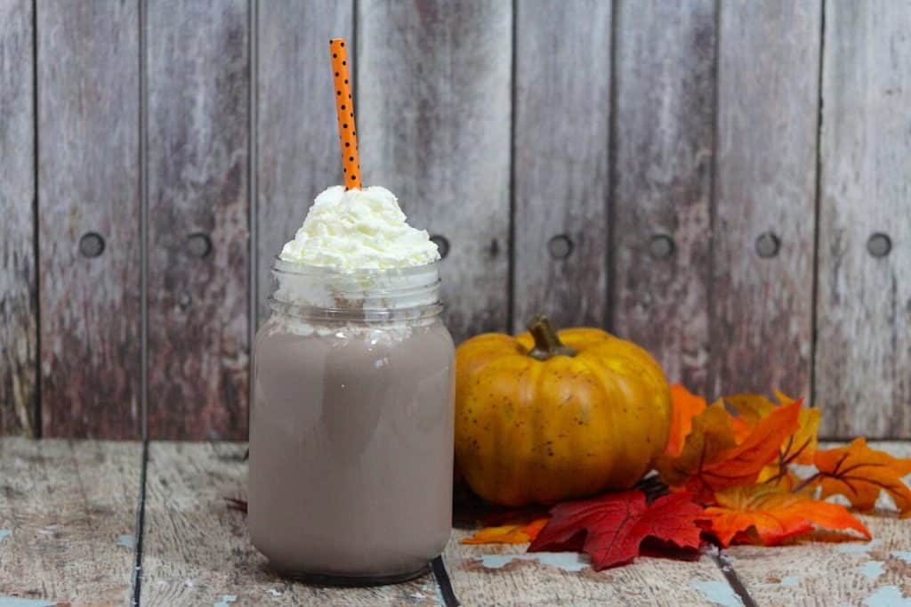 Hot chocolate in mason jar next to pumpkin