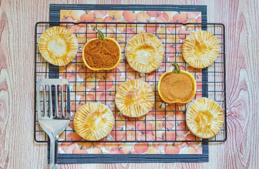 pumpkin hand pies on a cooling rack with pumpkin spice and filling