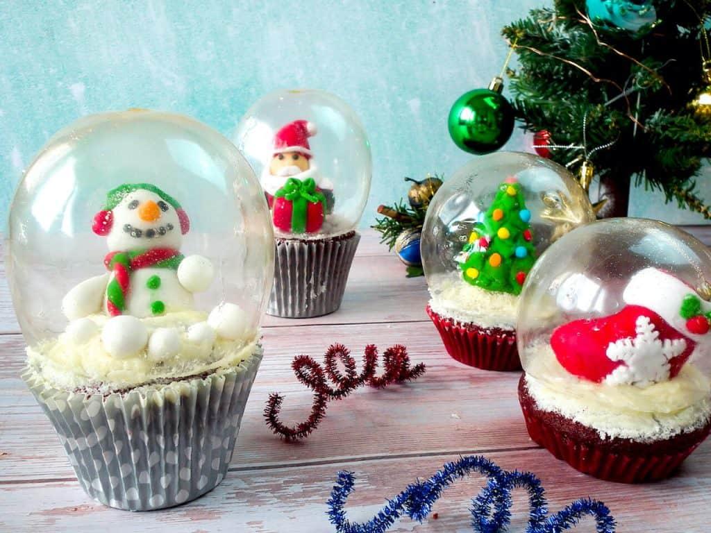 4 snow globe cupcakes with gelatin globe on top.